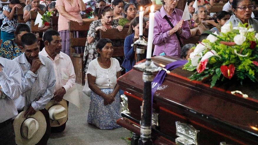 People pray by the coffin of slain Lesbia Janeth Urquia, an environmentalist and indigenous rights activist, during Mass in Marcala, Honduras, Friday, July 8, 2016. Authorities say Urquia's body was found Wednesday in a garbage dump in Marcala. Urquia's assassination comes four months after the murder of award-winning environmentalist Berta Caceres stirred international outrage. (AP Photo/Fernando Antonio)