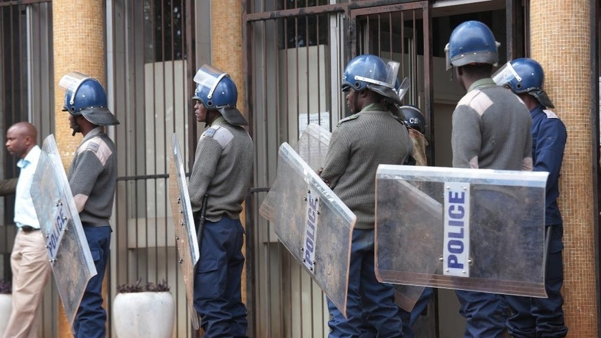 Police keep guard outside the Harare Magistrates Court in Harare, Wednesday, July 13, 2016. Zimbabwean pastor Evan Mawarire was charged Wednesday with attempting to overthrow a constitutionally elected government for organizing a nationwide strike which shut the country down last week. Water cannons and riot police surrounded the Harare Magistrates Court to prevent protests over Mawarire's court appearance. (AP Photo)