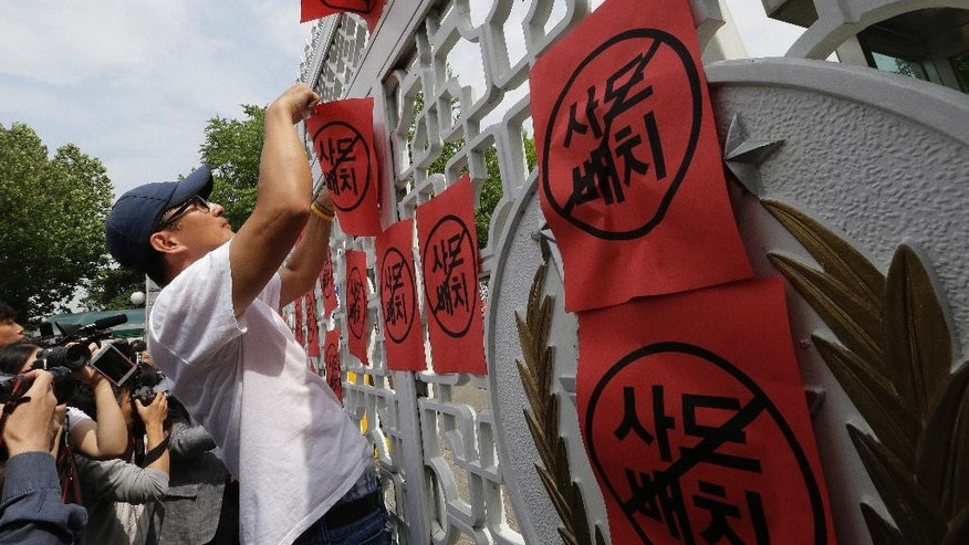 A protester pastes anti-THAAD banners on the gate of Defense Ministry during a rally to denounce deploying the Terminal High-Altitude Area Defense, or THAAD, in Seoul, South Korea, Wednesday, July 13, 2016. The site in South Korea that will be the base for an advanced U.S. missile defense system that the government says is designed to cope with North Korean threats will be announced Wednesday, Seoul officials said. (AP Photo/Ahn Young-joon)