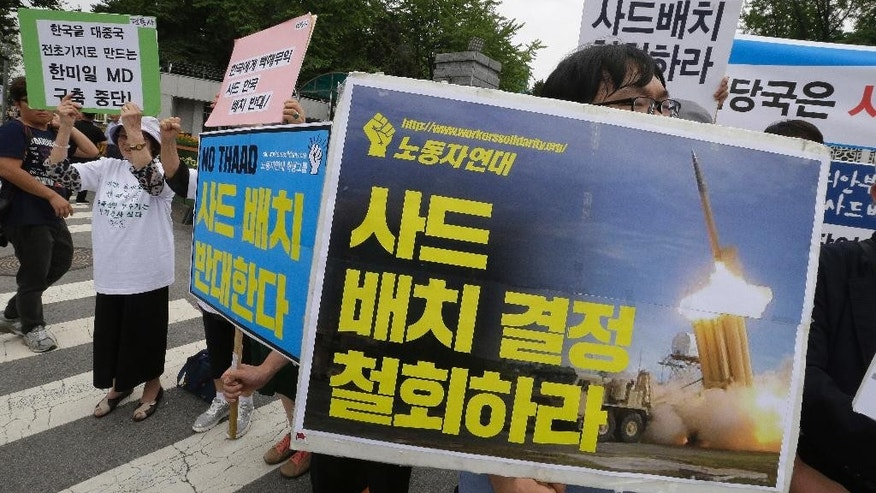 "Protesters stage a rally to denounce deploying the Terminal High-Altitude Area Defense (THAAD) in front of the Defense Ministry in Seoul, South Korea, Wednesday, July 13, 2016. The site in South Korea that will be the base for an advanced U.S. missile defense system that the government says is designed to cope with North Korean threats will be announced Wednesday, Seoul officials said. The banners read: ""Oppose deploying the THAAD."" (AP Photo/Ahn Young-joon)"