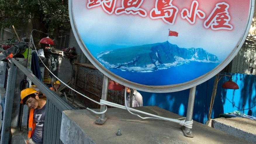 "A construction worker walks past an image of the Diaoyu Island used as the logo for a restaurant with the words ""Diaoyu Island little house"" in Beijing on Wednesday, July 13, 2016. China warned other countries Wednesday against threatening its security in the South China Sea after an international tribunal handed the Philippines a victory by saying Beijing had no legal basis for its expansive claims there.(AP Photo/Ng Han Guan)"