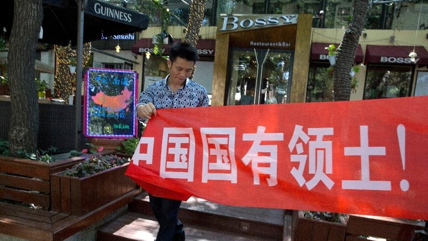 "A worker of a restaurant bar puts up a banner which partly reads: ""South China Sea is China's territory"" in Beijing Wednesday, July 13, 2016. China warned other countries Wednesday against threatening its security in the South China Sea after an international tribunal handed the Philippines a victory by saying Beijing had no legal basis for its expansive claims there. (AP Photo/Ng Han Guan)"