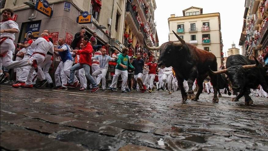 Revelers run beside Nunez del Cubillo's fighting bulls on the Estafeta corner during the seventh day of the running of the bulls at the San Fermin Festival, in Pamplona, northern Spain, Wednesday, July 13, 2016. An American was gored in the left leg and taken to a city hospital, spokesman said, and four other runners were hospitalized. Revelers from around the world flock to Pamplona every year to take part in the eight days of the running of the bulls. (AP Photo/Alvaro Barrientos)
