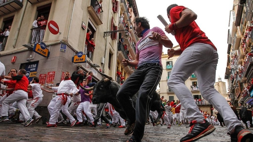 Revelers run around Nunez del Cubillo's fighting bulls on the Estafeta corner during the seventh running of the bulls at the San Fermin Festival, in Pamplona, northern Spain, Wednesday, July 13, 2016. An American was gored in the left leg and taken to a city hospital, spokesman said, and four other runners were hospitalized for contusions. Revelers from around the world flock to Pamplona every year to take part in the eight days of the running of the bulls. (AP Photo/Alvaro Barrientos)