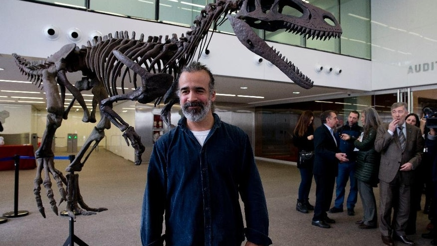 Argentine paleontologist Sebastian Apesteguia poses beside what he says is a replica of newly-discovered carnivorous dinosaur that lived in Argentina about 90 million discovered in Argentina's Patagonia in Buenos Aires, Argentina, Wednesday, July 13, 2016. The team of scientists says it was up to 26 feet long but its arms only measured about 2 feet. (AP Photo/Natacha Pisarenko)