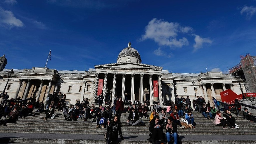 FILE - A Thursday, Feb. 11, 2016 file photo showing people resting and taking their lunch break on the stairs at Trafalgar Square in London, with the National Gallery at rear. Theresa May arrives at 10 Downing Street at an odd, supercharged moment when Britain is gripped by uncertainty. The country is relatively prosperous and at peace, its streets free of trouble and its commerce strong. Yet British citizens have chosen to reset the country's compass, steering it away from the European Union with its finicky rules and regulations and its wide open borders, and sending it back in time to what is remembered as a prouder era when Britain stood alone, defiant. (AP Photo/Frank Augstein, File)