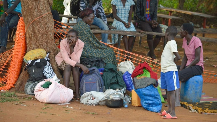 In this Tuesday July 12, 2016 photo, people take shelter near the All Saints Church in Juba, South Sudan. Embassies and aid organizations in South Sudan were trying to evacuate staff from the capital, Juba, on Tuesday as a precarious calm settled over the city following several days of deadly clashes. (AP Photo)