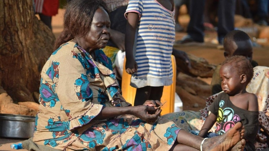 In this Tuesday July 12, 2016 photo, a woman sits with her child near a church in Juba, South Sudan. Embassies and aid organizations in South Sudan were trying to evacuate staff from the capital, Juba, on Tuesday as a precarious calm settled over the city following several days of deadly clashes. (AP Photo)