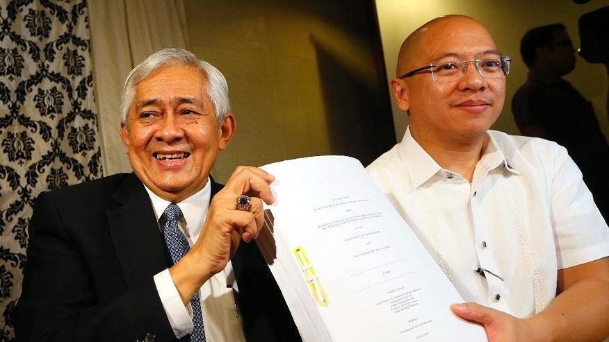 Associate Justice of the Supreme Court Francis Jardeleza, left, and former Solicitor General Florin Hilbay hold a photocopy of the Hague-based U.N. international arbitration tribunal ruling favoring the Philippines in its case against China on the dispute on South China Sea following a news conference Wednesday, July 13, 2016 in Manila, Philippines. The Permanent Court of Arbitration (PCA) issued its ruling Tuesday in The Hague in response to an arbitration case brought by the Philippines against China regarding the South China Sea, saying that any historic rights to resources that China may have had were wiped out if they are incompatible with exclusive economic zones established under a U.N. treaty. Jardeleza and Hilbay were members of the Philippine team who filed the case against China in The Hague. (AP Photo/Bullit Marquez)