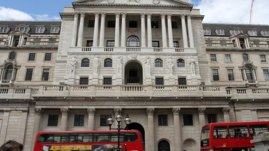 Buses and pedestrians pass the Bank of England in London on Thursday July 14, 2016. The Bank of England surprised financial markets by opting against cutting interest rates on Thursday, despite clear evidence of the initial economic damage caused by the country's vote last month to leave the European Union. (AP Photo/Adela Suliman)
