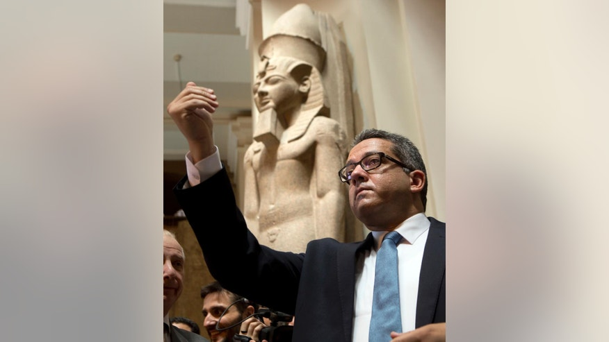 Egyptian Antiquities Minister Khaled el-Anani speaks during the opening of King Khufu papyri collections discovered at Wadi El-Jarf port, as it is on display for the first time at the Egyptian museum in Cairo, Egypt, Thursday, July 14, 2016. Ancient statue of king Ramesses II at background. (AP Photo/Amr Nabil)