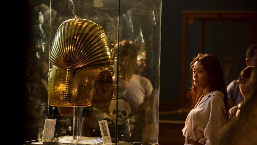 Visitors look at the gold mask of King Tutankhamun in a glass case, at the Egyptian museum in Cairo, Egypt, Thursday, July 14, 2016. (AP Photo/Amr Nabil)