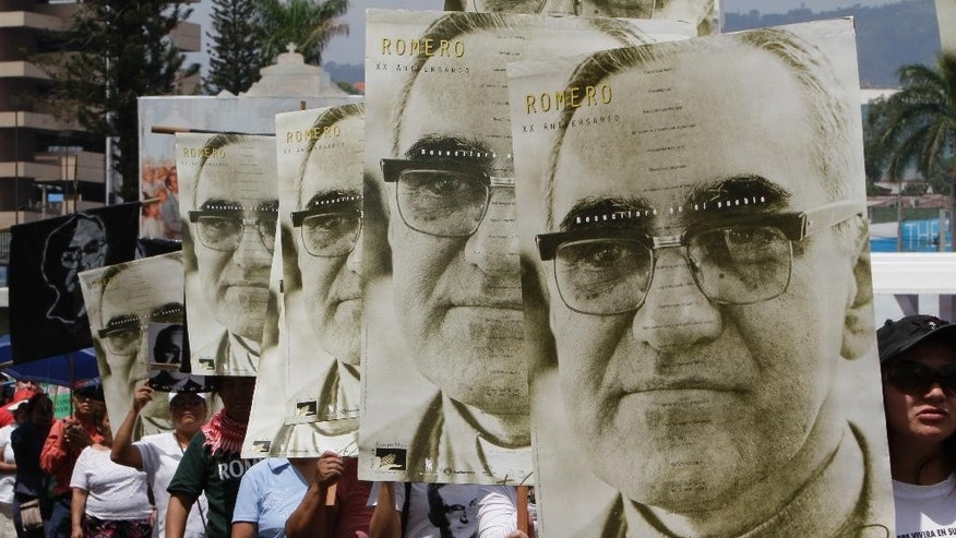 FILE - In this March 24, 2011 file photo, protesters carry portraits of slain Archbishop Oscar Arnulfo Romero on the 31st anniversary of his death in San Salvador, El Salvador. Perpetrators of human rights violations during El Salvador's civil war such as Romero's 1980 assassination could be prosecuted now that the country's Supreme Court struck down an amnesty law protecting them, in a July 13, 2016 decision. Romero was fatally shot on orders by an official in El Salvador's U.S.-backed army as he celebrated Mass. (AP Photo/Luis Romero, File)