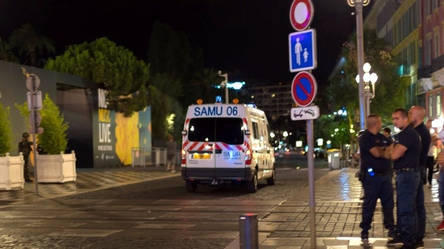 "An ambulance and police officers are seen  after a truck drove on to the sidewalk and plowed through a crowd of revelers who'd gathered to watch the fireworks in the French resort city of Nice, southern France, Friday, July 15, 2016. A spokesman for France's Interior Ministry says there are likely to be ""several dozen dead"" after a truck drove into a crowd of revelers celebrating Bastille Day in the French city of Nice. (AP Photo/Ciaran Fahey)"