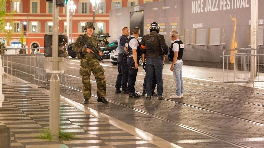 "Police officers and a soldier stand by the sealed off area of an attack after a truck drove on to the sidewalk and plowed through a crowd of revelers who'd gathered to watch the fireworks in the French resort city of Nice, southern France, Friday, July 15, 2016. A spokesman for France's Interior Ministry says there are likely to be ""several dozen dead"" after a truck drove into a crowd of revelers celebrating Bastille Day in the French city of Nice. (AP Photo/Ciaran Fahey)"