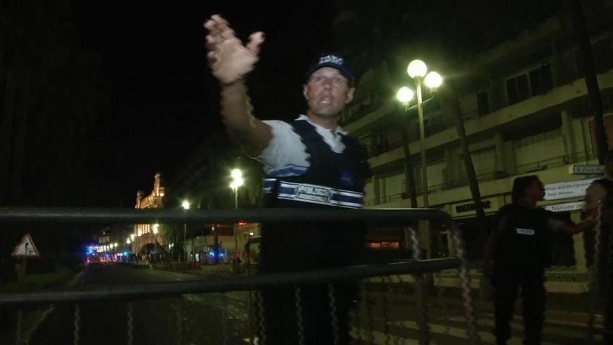 In this video grab taken Thursday July 14, 2016, a policeman chase people out of the cordoned-off area after a truck drove on to the sidewalk and plowed through a crowd of revelers who'd gathered to watch the fireworks in the French resort city of Nice. Officials and eyewitnesses described as a deliberate attack. There appeared to be many casualties. (BFMTV via AP)