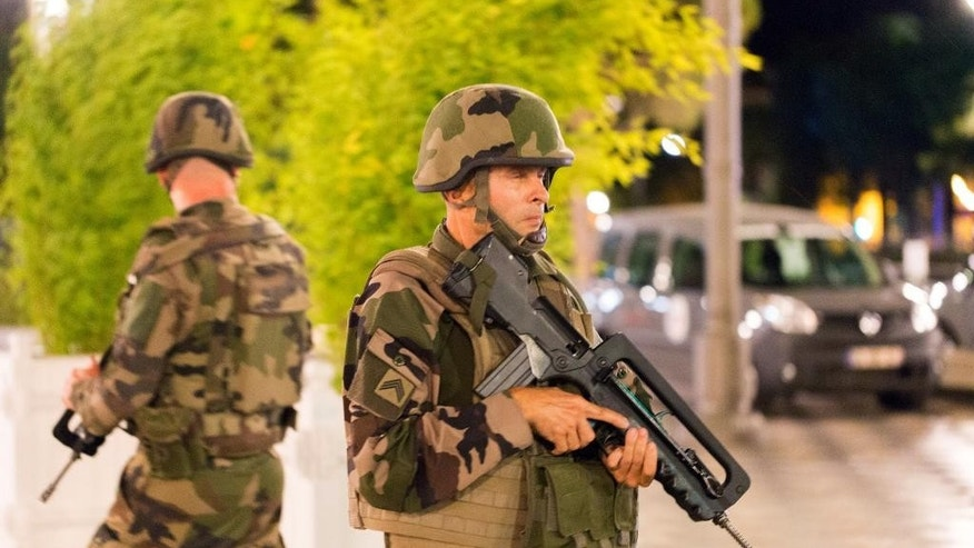 "French soldiers stand guard by the sealed off area of an attack after a truck drove on to the sidewalk and plowed through a crowd of revelers who'd gathered to watch the fireworks in the French resort city of Nice, southern France, Friday, July 15, 2016. A spokesman for France's Interior Ministry says there are likely to be ""several dozen dead"" after a truck drove into a crowd of revelers celebrating Bastille Day in the French city of Nice. (AP Photo/Ciaran Fahey)"