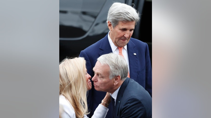 U.S Secretary of State John Kerry, top, looks down as French Foreign Minister Jean-Marc Ayrault kisses U.S ambassador to France Jane Hartley  on the Champs Elysees avenue before the Bastille Day Parade in Paris, Thursday, July 14, 2016. (AP Photo/Francois Mori)