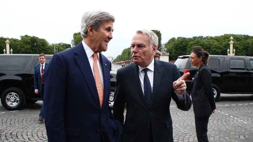French Foreign Minister Jean-Marc Ayrault, right, welcomes U.S Secretary of State John Kerry on the Champs Elysees avenue before the Bastille Day Parade in Paris, Thursday, July 14, 2016. (AP Photo/Thibault Camus, Pool)