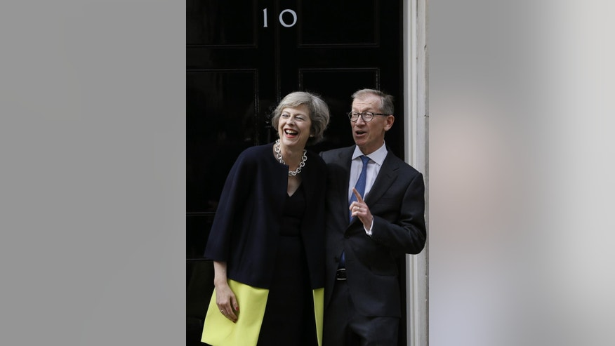 New British Prime Minister Theresa May and her husband Philip May stand on the steps of 10 Downing Street in London, Wednesday July 13, 2016. David Cameron stepped down Wednesday after six years as prime minister. (AP Photo/Kirsty Wigglesworth)