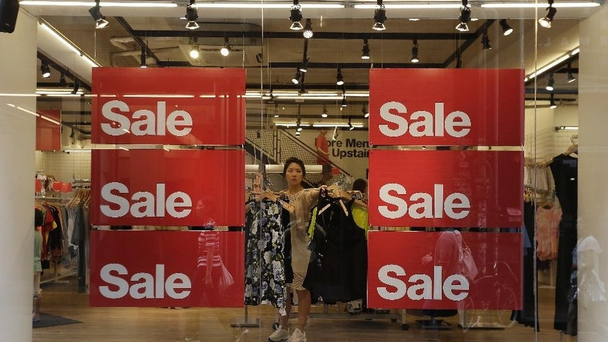 A shopper looks at clothes next to discount sale signs at a store in Seoul, South Korea, Thursday, July 14, 2016. South Korea's central bank has lowered its growth outlook on Asia's fourth-largest economy citing Britain's decision to leave the European Union. (AP Photo/Ahn Young-joon)