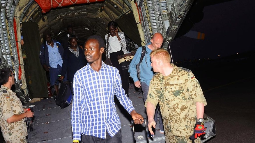 Aid workers and civilians arrive from Juba to Entebbe airport in Uganda, Wednesday, July, 13, 2016. Commercial flights to Juba remain cancelled though charter flights are evacuating hundreds of aid workers and other foreign citizens from the capital. The U.S. military in Africa says it has sent 40 additional soldiers to South Sudan's capital, Juba, to help secure American personnel and facilities in the war-torn city. (AP Photo/Ronald Kabuubi)