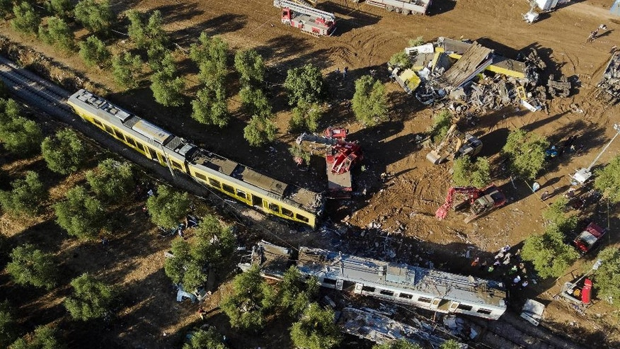 """Aerial view , Wednesday, July 13, 2016, of the site of a railway disaster the day after an head-on collision between two trains near Andria, in the southern Italian region of Apulia. Italian officials on Wednesday pointed to delayed, EU-financed rail improvements and the """"risky,"""" antiquated telephone alert system used in parts of Italy as possible underlying causes of a violent head-on train crash that killed some two dozen people. (AP Photo/Localteam.it)"""