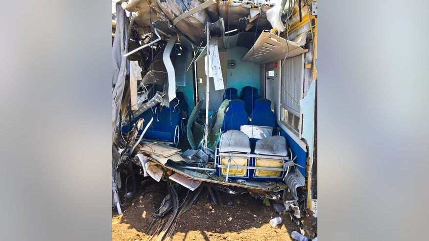 The wreckage of a carriage lies on a field near the railroad as recovery operations continued a day after two commuter trains slammed into one another just before noon Tuesday in Puglia, between the towns of Corato and Andria, Italy, Wednesday, July 13, 2016. Delayed rail improvements and the antiquated telephone alert system will be considered as part of the investigation into the violent head-on train crash in southern Italy that killed nearly two dozen people, officials said Wednesday. (Milena di Mauro/ANSA via AP)