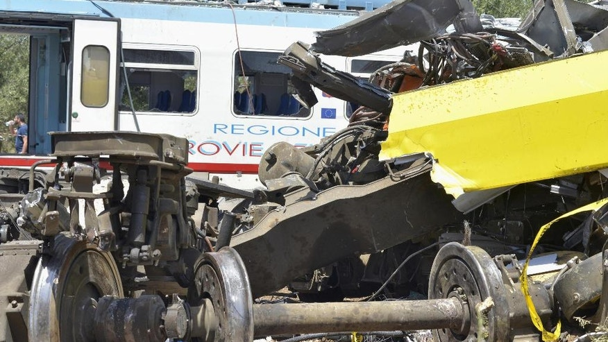 The wreckage of a carriage lies on a field near the railroad as recovery operations continued a day after two commuter trains slammed into one another just before noon Tuesday in Puglia, between the towns of Corato and Andria, Italy, Wednesday, July 13, 2016. Delayed rail improvements and the antiquated telephone alert system will be considered as part of the investigation into the violent head-on train crash in southern Italy that killed nearly two dozen people, officials said Wednesday. (Gaetano Lo Porto/ANSA via AP)