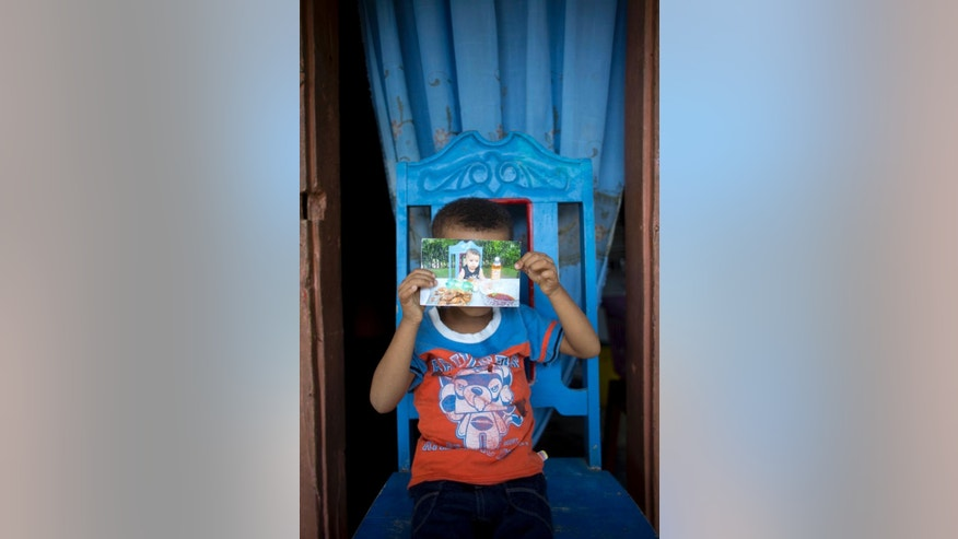 "In this June 24, 2016 photo, five-year-old Anderson Joseph holds a picture of himself at 6 month of age, during his baptism, at his grand mother's home in Port Salut, Haiti. Anderson is the result of a liaison between Uruguayan marine Julio Cesar Posse and a local Haitian woman. ""He promised me he'd marry me and would take care of me,"" his mother, now 22, tearfully said. (AP Photo/Dieu Nalio Chery)"
