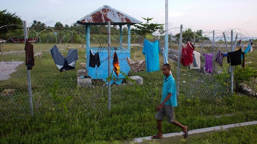 In this June 24, 2016 photo, a resident walks next to a former Uruguayan U.N. peacekeeper base in Port Salut, Haiti. A U.N. official confirmed that four Port Salut women have paternity established in 2014 after DNA swabs from the mothers, children and peacekeepers were analyzed. (AP Photo/Dieu Nalio Chery)