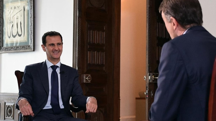 In this photo released on Thursday, July 14, 2016, by the Syrian official news agency SANA, Syrian President Bashar Assad, left, speaks during an interview with American network NBC News, in Damascus, Syria. Assad said he does not know who killed U.S.-born journalist Marie Colvin, whose relatives have filed a lawsuit in U.S. federal court claiming that Syrian government officials targeted and killed her in 2012 to silence her reporting on Syria and the besieged city of Homs. (SANA via AP)