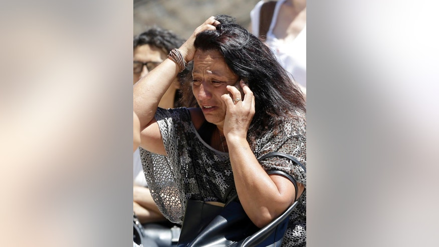 An unidentified relative of the victims of the Bastille Day attack reacts as she makes a phone call in front of Pasteur Hospital in Nice, southern France, Friday, July 15, 2016. A large truck mowed through revelers gathered for Bastille Day fireworks in Nice, killing more than 80 people and sending people fleeing into the sea as it bore down for more than a mile along the Riviera city's famed waterfront promenade. (AP Photo/Claude Paris)