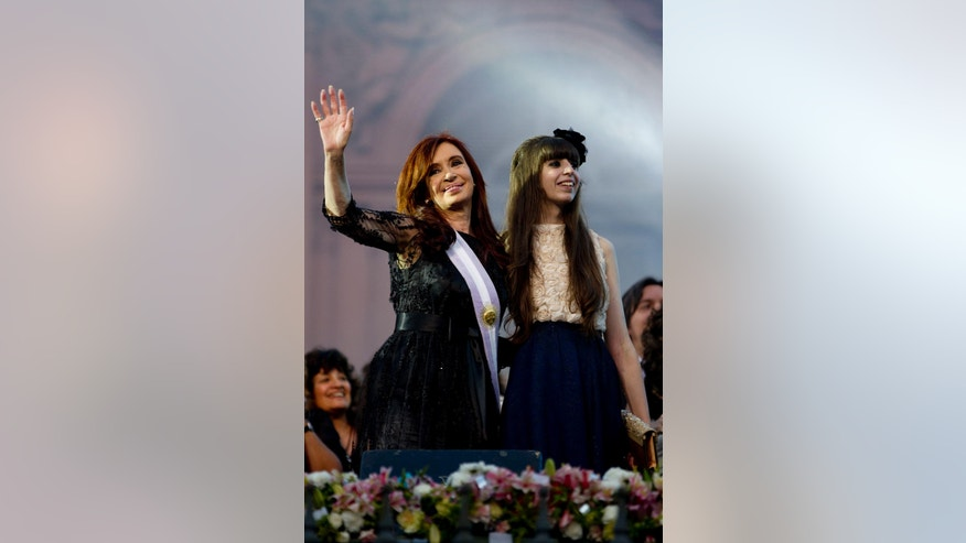 FILE - In this Dec. 10, 2011 file photo, Argentina's President Cristina Fernandez, left, accompanied by her daughter Florencia Kirchner, waves to supporters after her swearing-in ceremony at the government house in Buenos Aires, Argentina. An Argentine prosecutor asked on Friday, July 15, 2016, a local court to seize the more than $4.6 million from the bank safe deposit boxes belonging to the 26-year-old Kirchner, as part of an investigation into alleged money laundering.  (AP Photo/Natacha Pisarenko, File)