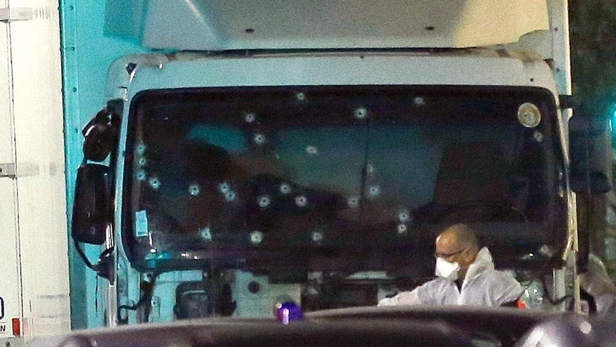 A forensic officer stands near a van with its windscreen riddled with bullets, that plowed through a crowd of revelers who'd gathered to watch the fireworks in the French resort city of Nice, southern France, Friday, July 15, 2016. At least 80 people were killed before police killed the driver, authorities said. (AP Photo/Claude Paris)