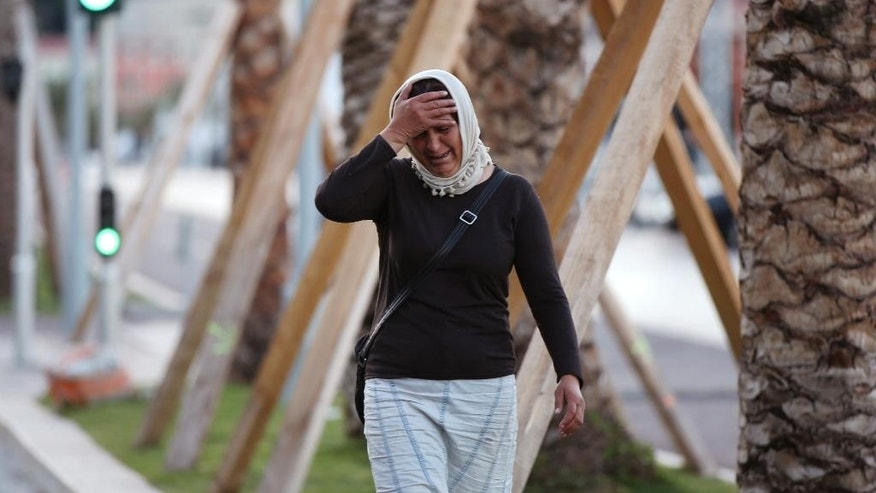 A woman cries asking for her son as she walk near the scene of an attack after a truck drove onto the sidewalk and plowed through a crowd of revelers who'd gathered to watch the fireworks in the French resort city of Nice, southern France, Friday, July 15, 2016.  (AP Photo/Luca Bruno)