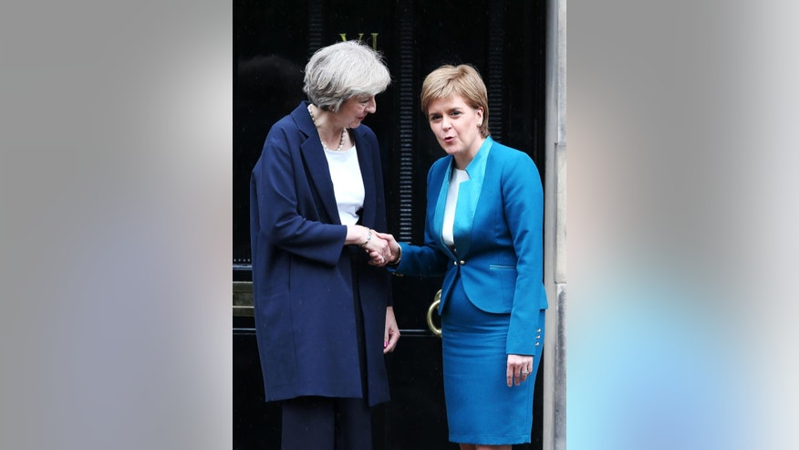 Britain's Prime Minister Theresa May, left, is greeted by Scotland's First Minister Nicola Sturgeon at Bute House in Edinburgh, Scotland, Friday July 15, 2016.  Theresa May traveled to Scotland on her first official trip as prime minister to sooth fears in Scotland about the impact of Britain leaving the European Union. (Andrew Milligan / PA via AP)