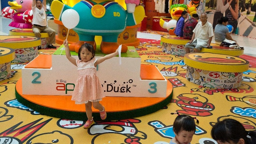 A child poses for photos near display of merchandise at a shopping mall in Beijing, China, Friday, July 15, 2016. China's economic growth held steady in the most recent quarter, according to official data released Friday, indicating policies meant to counter the slowdown in the world's second biggest economy are paying off for the moment.(AP Photo/Ng Han Guan)