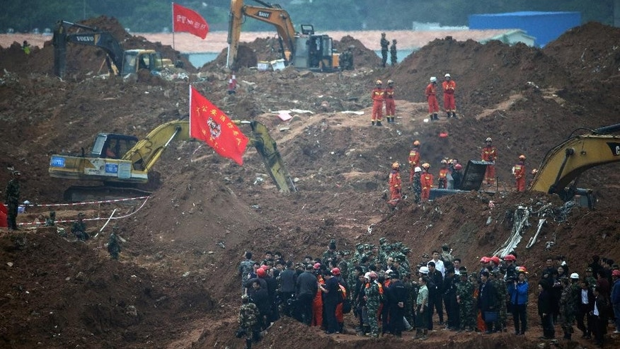 FILE - In this Dec. 22, 2015 file photo, government officials led by head of the rescue units look at the rescuers conducting search and rescue operation following a landslide at an industrial park in Shenzhen in south China's Guangdong province. China's Cabinet said Friday, July 15, 2016 that 53 people are in custody in an investigation into the landslide that killed 73 people and left four others missing last year. (AP Photo/Andy Wong, File)