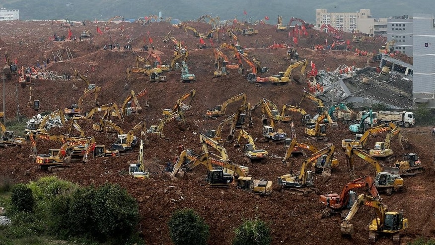 FILE - In this Tuesday, Dec. 22, 2015 file photo, rescuers search for potential survivors following a landslide at an industrial park in Shenzhen in south China's Guangdong province. China's Cabinet said Friday, July 15, 2016 that 53 people are in custody in an investigation into the landslide that killed 73 people and left four others missing last year. (AP Photo/Andy Wong, file)