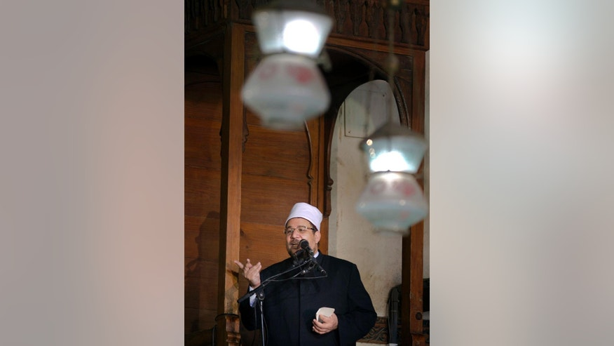 Mokhtar Gomaa, Egypt's minister of religious endowment, holds a piece of paper and reads out a standardized sermon, which was prepared by the ministry's scholars, at Amr Ibn al-As mosque, in Cairo, Egypt, Friday, July 15, 2016. The government is promoting the standardized sermons as part of its efforts to reform the religious discourse and curbing extremism. (AP Photo/Amr Nabil)