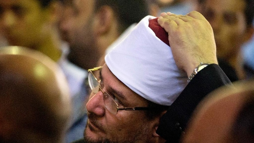 "Mokhtar Gomaa, Egypt's minister of religious endowments, adjusts his ""Emamah,"" a head cover for Muslim clerics, after he delivered a standardized sermon, which was prepared by the ministry's scholars, at Amr Ibn al-As mosque, in Cairo, Egypt, Friday, July 15, 2016. The government is promoting the standardized sermons as part of its efforts to reform the religious discourse and curbing extremism. (AP Photo/Amr Nabil)"