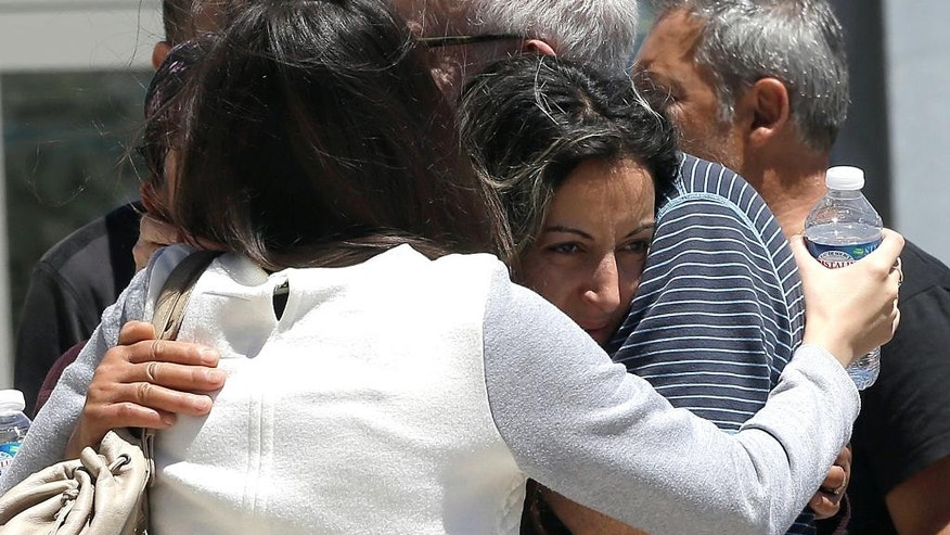Relative of the victims of the Bastille Day attack confort each other as they gather in front of Pasteur Hospital in Nice, southern France, Friday, July 15, 2016. A large truck mowed through revelers gathered for Bastille Day fireworks in Nice, killing more than 80 people and sending people fleeing into the sea as it bore down for more than a mile along the Riviera city's famed waterfront promenade. (AP Photo/Claude Paris)