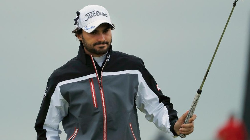 Clement Sordet of France raises his club on the 7th green, wearing a cap that has the words 'Pray for Nice' written by hand on it, during the second round of the British Open Golf Championship at the Royal Troon Golf Club in Troon, Scotland, Friday, July 15, 2016. France was ravaged by its third attack in two years when a large white truck mowed through revelers gathered for Bastille Day fireworks in Nice, late Thursday, as it bore down on the crowd for more than a mile along the Riviera city's famed seaside promenade(AP Photo/Ben Curtis)