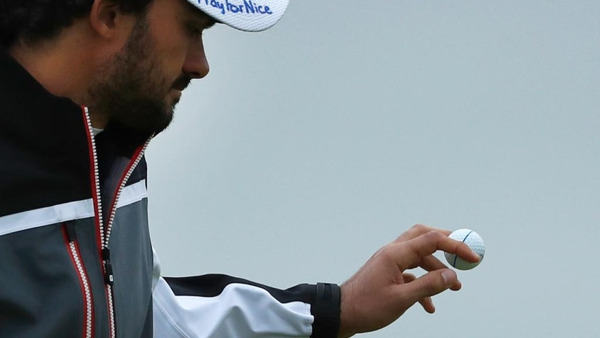 Clement Sordet of France picks up his ball on the 7th green, wearing a cap that has the words 'Pray for Nice' written by hand on it, during the second round of the British Open Golf Championship at the Royal Troon Golf Club in Troon, Scotland, Friday, July 15, 2016. France was ravaged by its third attack in two years when a large white truck mowed through revelers gathered for Bastille Day fireworks in Nice, late Thursday, as it bore down on the crowd for more than a mile along the Riviera city's famed seaside promenade(AP Photo/Ben Curtis)