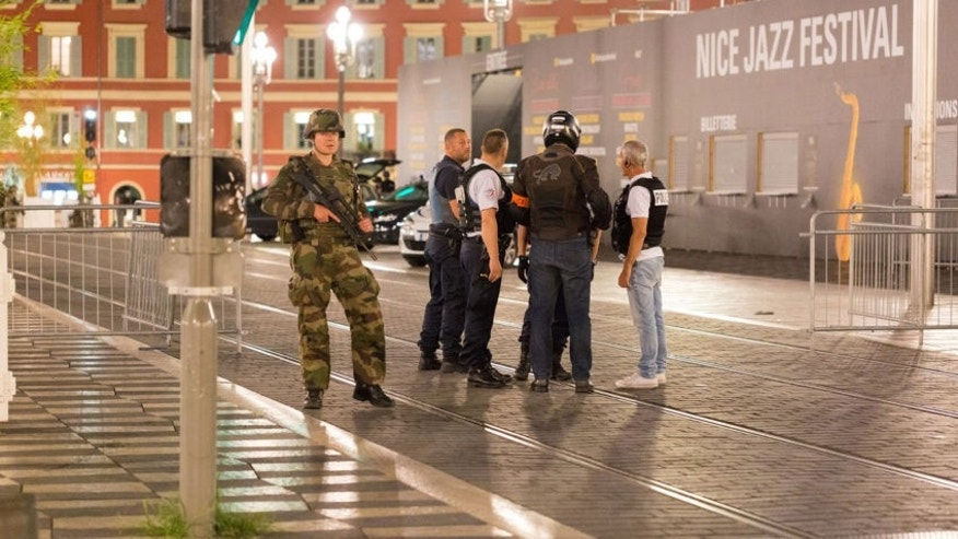 Police and a soldier stand by crime scene after a truck drove onto a crowded Nice promenade Thursday, killing at least 84. (AP)
