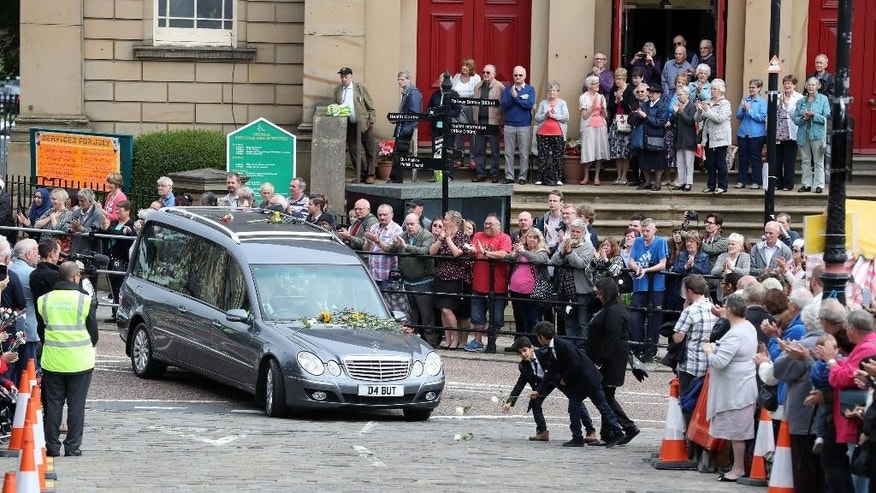 Mourners throw roses as the hearse carrying the coffin of MP Jo Cox passes in Batley, England ahead of her private funeral service Friday July 15, 2016. The mother of two young children died on June 16, 2016 after she was attacked outside a library in Birstall, England. (Owen Humphreys/PA via AP)