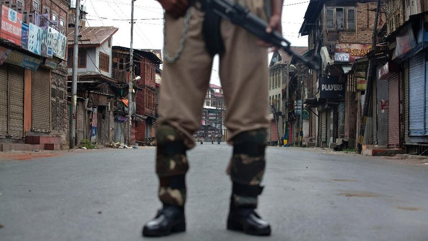Indian paramilitary soldiers stand guard during a curfew in Srinagar, Indian controlled Kashmir, Friday, July 15, 2016. Curfew imposed in the disputed Himalayan region continued for the seventh straight day to check anti-India violence following the recent killing of  a charismatic Kashmiri insurgent Burhan Wani. (AP Photo/Dar Yasin)