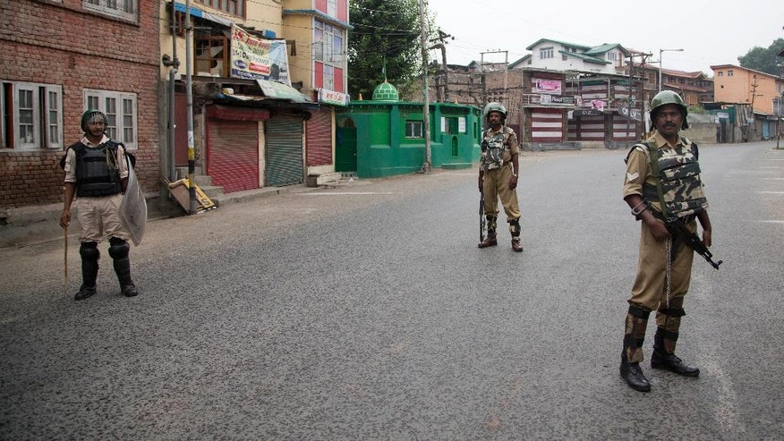 Indian paramilitary soldiers stand guard during a curfew in Srinagar, Indian controlled Kashmir, Friday, July 15, 2016. Curfew imposed in the disputed Himalayan region continued for the seventh straight day to check anti-India violence following the recent killing of Burhan Wani, chief of operations of Hizbul Mujahideen, Kashmir's largest rebel group. (AP Photo/Dar Yasin)