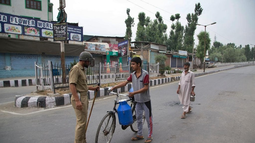 A policeman checks a civilian at a temporary check post during a curfew in Srinagar, Indian controlled Kashmir, Friday, July 15, 2016. Curfew imposed in the disputed Himalayan region continued for the seventh straight day to check anti-India violence following the recent killing of Burhan Wani, chief of operations of Hizbul Mujahideen, Kashmir's largest rebel group. (AP Photo/Dar Yasin)